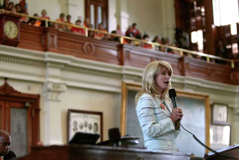 Sen. Wendy Davis speaks during a June 25, 2013, filibuster intended to stop Senate Bill 5, which contains restrictions on abortions after 20 weeks, at the State Capitol in Austin. She was on her feet in pink running shoes for about 11 hours, drawing attention, fans, detractors and instant celebrity. Photo: ERICH SCHLEGEL / NYTNS