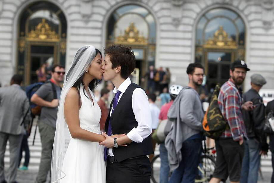 Jenni Chang (left) and Lisa Dazols, both of San Francisco, kiss outside City Hall. They've had a ceremony at Russian River, and now are waiting to have an official wedding. Photo: Lea Suzuki, The Chronicle