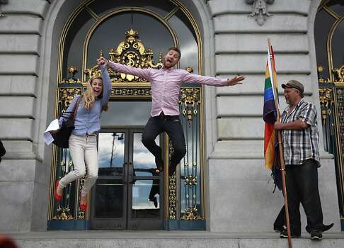 Abbie Coffee (l to r) and Matthew Ridenour, both of San Francisco,  have a bystander take a photo of them after they signed their marriage license at City Hall as Bob Sodervick watches on Wednesday, June 26, 2013 in San Francisco,  Calif.  Ridenour said they were happy to be celebrating their signing as well as the Supreme Courts decisions. The Supreme Court handed down their decisions dismissing California's Proposition 8 and striking down the Defense of Marriage Act. Photo: Lea Suzuki, The Chronicle