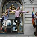 Abbie Coffee (l to r) and Matthew Ridenour, both of San Francisco,  have a bystander take a photo of them after they signed their marriage license at City Hall as Bob Sodervick watches on Wednesday, June 26, 2013 in San Francisco,  Calif.  Ridenour said they were happy to be celebrating their signing as well as the Supreme Courts decisions. The Supreme Court handed down their decisions dismissing California's Proposition 8 and striking down the Defense of Marriage Act.