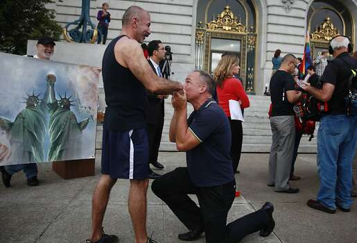 Crispin Hollings (right) proposes to Luis Casillas (right), both of San Francisco, at City Hall on Wednesday, June 26, 2013 in San Francisco,  Calif.  Hollings had proposed earlier in the morning as listened to the Supreme Court rulings from outside of City Hall.The Supreme Court handed down their decisions dismissing California's Proposition 8 and striking down the Defense of Marriage Act. Photo: Lea Suzuki, The Chronicle