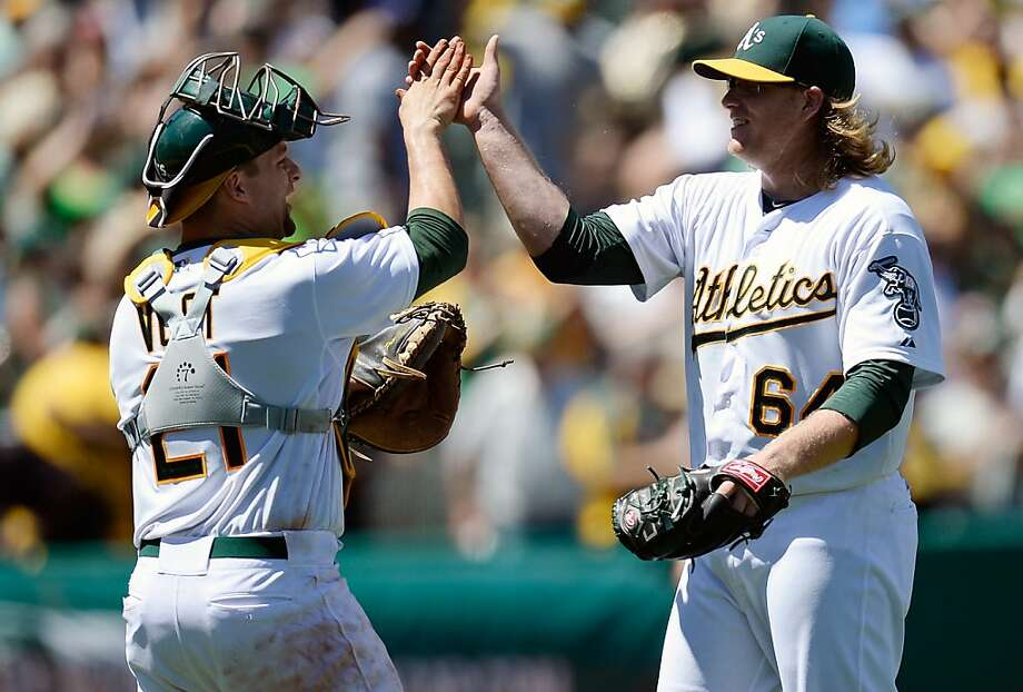 OAKLAND, CA - JUNE 26:  A.J. Griffin #64 and Stephen Vogt #21 of the Oakland Athletics celebrate defeating the Cincinnati Reds 5-0 at O.co Coliseum on June 26, 2013 in Oakland, California. Griffin pitched a two-hit complete game shutout, the first of his career. The Athletics defeated the Reds 5-0. (Photo by Thearon W. Henderson/Getty Images) Photo: Thearon W. Henderson, Getty Images