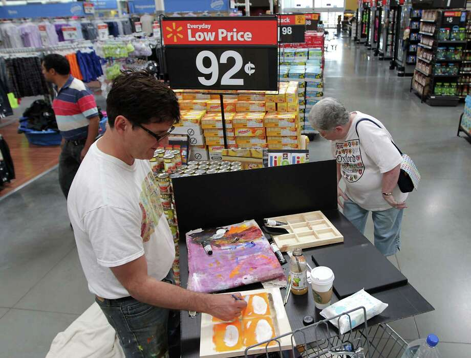 "Nationally-known artist Brendan O'Connell, left, who's become famous as ""Walmart's Warhol,"" paints as Nancy Fleming right, looks on during O'Connell's visit to the Heights Walmart. O'Connell uses the people and products in Walmart stores to represent the American consumer experience Wednesday, June 26, 2013, in Houston. His oil paintings now sell for thousands of dollars, but there was a time store managers kicked him out when they caught O'Connell taking photos. Photo: James Nielsen, Houston Chronicle / © 2013  Houston Chronicle"