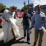 Jerry Deal, left, wears his wedding gown as he and Marvin Dunson and Ted Garey walk through the Castro district to celebrates the United States Supreme Court ruling that Section 3 of the federal Defense of Marriage Act is unconstitutional and that California's Proposition 8 has been struck down, Wednesday June 26, 2013, in San Francisco, Calif.