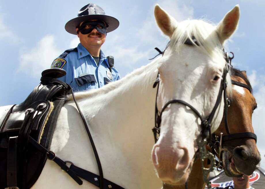 Houston Police officer Bart Catlett wears a Lone Ranger mask as he and his horse, Toby, stand next to Silver during a ceremony inducting the famous white horse at an honorary member of the HPD Mounted Patrol at Discovery Green Wednesday, June 26, 2013, in Houston. Photo: Brett Coomer, Houston Chronicle / © 2013 Houston Chronicle