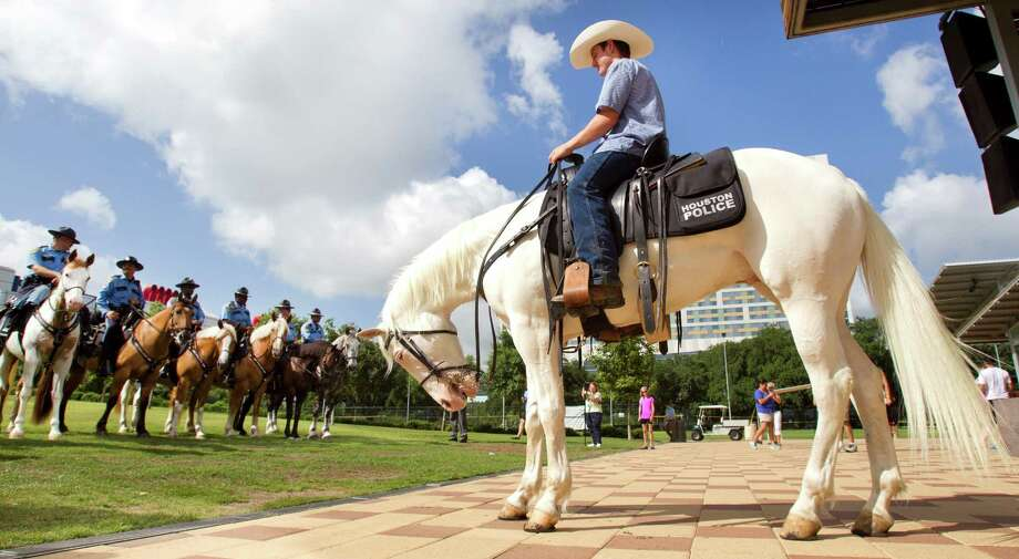 Tanner Lovegren sits atop Silver with officers from the Houston Police Mounted Patrol during a ceremony inducting The Lone Ranger's horse as an honorary member of HPD's Mounted Patrol at Discovery Green Wednesday, June 26, 2013, in Houston. Photo: Brett Coomer, Houston Chronicle / © 2013 Houston Chronicle
