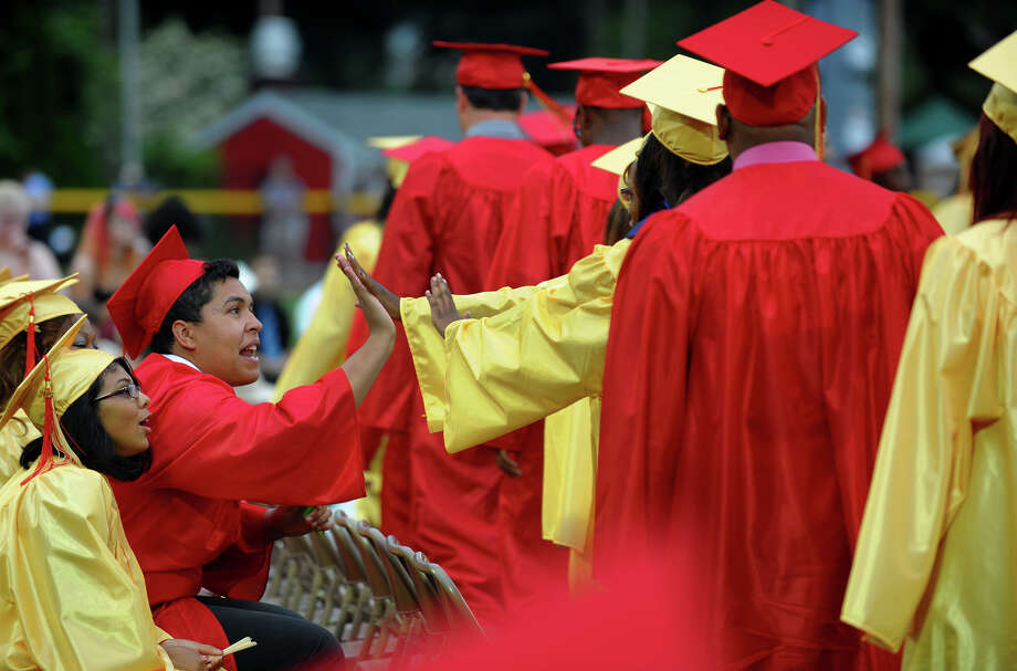 Graduate Isaac DeAssis high fives fellow graduates as they walk up to get their diplomas during Stratford High School's 124th Annual Commencement in Stratford, Conn. on Wednesday June 26, 2013. Photo: Christian Abraham / Connecticut Post