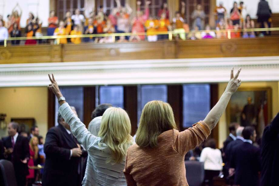 In this Tuesday, June 25, 2013 photo, Texas state Senators Wendy Davis, left, and Sylvia R. Garcia cast their votes against Senate Bill 5 amidst the cheers of the Senate Gallery, in Austin, Texas.  As she spoke late into the night, railing against proposed abortion restrictions, Davis, a former Texas teen mom, catapulted from little-known junior state senator to national political superstar in pink tennis shoes. Photo: Emily Ng, Associated Press