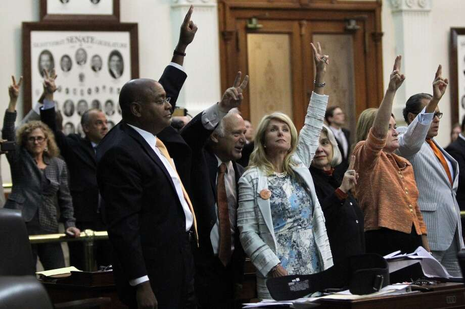 State Senator Wendy Davis, center, celebrates with colleagues as bedlam breaks out near midnight on the final day of the legislative special session, as the Senate considers an abortion bill, June 25, 2013, in Austin, Texas. Photo: Louis DeLuca, McClatchy-Tribune News Service