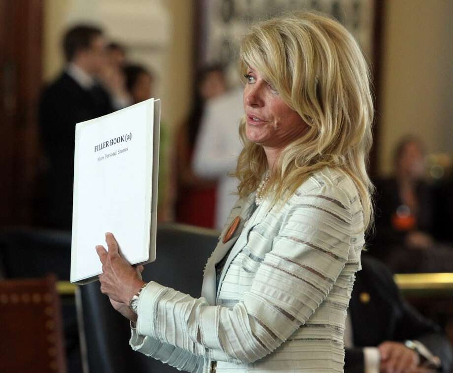 State Senator Wendy Davis gets more material to read during the seventh hour of filibustering during the final day of the legislative special session, as the Senate considers an abortion bill, June 25, 2013, in Austin, Texas. Photo: Louis DeLuca, McClatchy-Tribune News Service