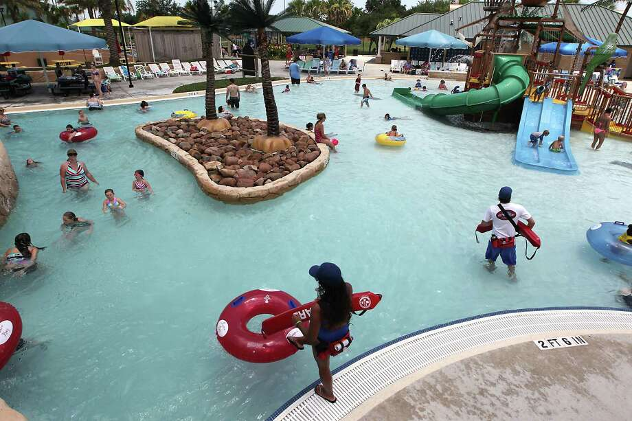 A lifeguard stands near the spot where a 4-year-old boy was found unconscious and pulled from the water in the Pirates Bay Water Park in late May, Wednesday, June 26, 2013, in Baytown. The boy had reportedly been in the ankle-deep toddler's area when he veered into a gradually deeper part near the Lazy River area, which has a maximum depth of about 4 feet. Photo: James Nielsen, Houston Chronicle / © 2013  Houston Chronicle