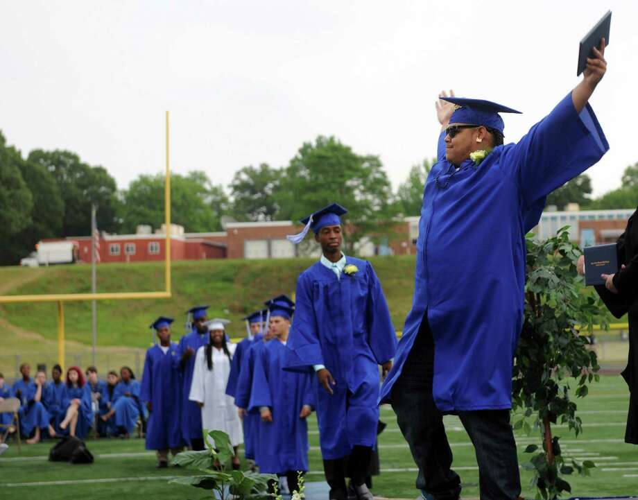 Graduate Jocquan Hart throws his arms up during commencement at Bunnell High School in Stratford, Conn. Wednesday, June 26, 2013. Photo: Autumn Driscoll / Connecticut Post