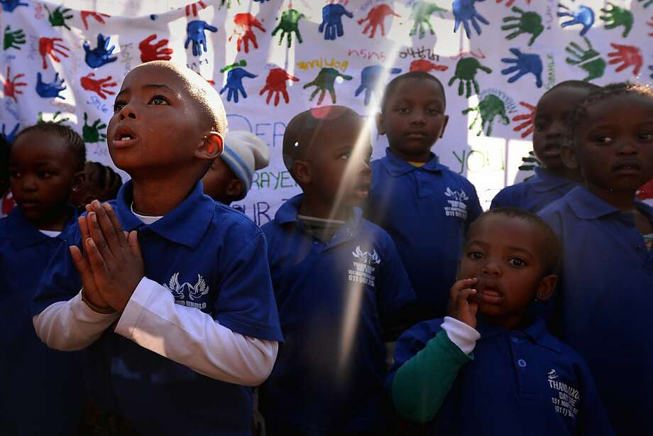 PRETORIA, SOUTH AFRICA - JUNE 26:  Children gather to leave messages of support for former South African President Nelson Mandela outside the Mediclinic Heart Hospital June 26, 2013 in Pretoria, South Africa. South African President Jacob Zuma confirmed on June 23 that Mandela's condition has become critical since he was admitted to the hospital over two weeks ago for a recurring lung infection.  (Photo by Jeff J Mitchell/Getty Images) Photo: Jeff J Mitchell, Getty Images