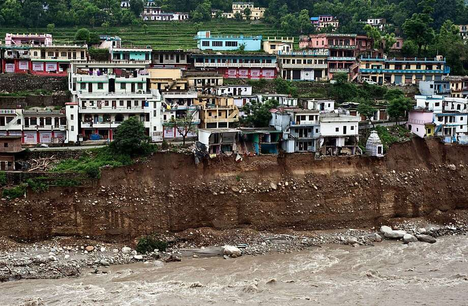 Damaged houses are seen precariously above the flash flood-eroded Mandakini river in the town of Tilwara, around 30kms from Rudraprayag, on June 26, 2013. Around 1,000 people have been killed in flash floods and landslides in northern India, as a top official warned June 24 that rebuilding of the devastated Himalayan region would take years.   AFP PHOTO/MANAN VATSYAYANAMANAN VATSYAYANA/AFP/Getty Images Photo: Manan Vatsyayana, AFP/Getty Images