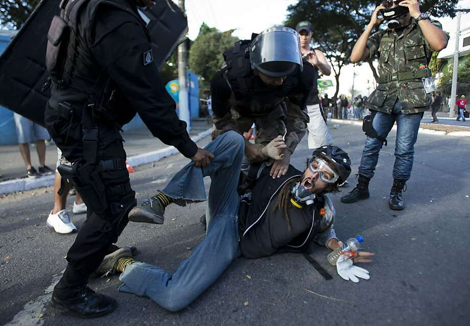 Riot police detain a man during a demonstration in Belo Horizonte, Brazil, Wednesday, June 26, 2013.  Brazilian anti-government protesters in part angered by the billions spent in World Cup preparations and police clashed Wednesday near the stadium hosting a Confederations Cup football match, with tens of thousands of demonstrators trying to march on the site confronting police firing tear gas and rubber bullets.(AP Photo/Victor R. Caivano) Photo: Victor R. Caivano, Associated Press