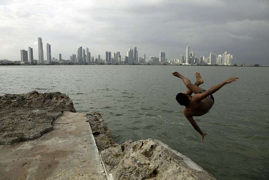 Backdropped by the skyline of Panama City, a boy jumps into Panama Bay, looking out from the colonial neighborhood of Casco Viejo, Wednesday, June 26, 2013. (AP Photo/Arnulfo Franco) Photo: Arnulfo Franco, Associated Press