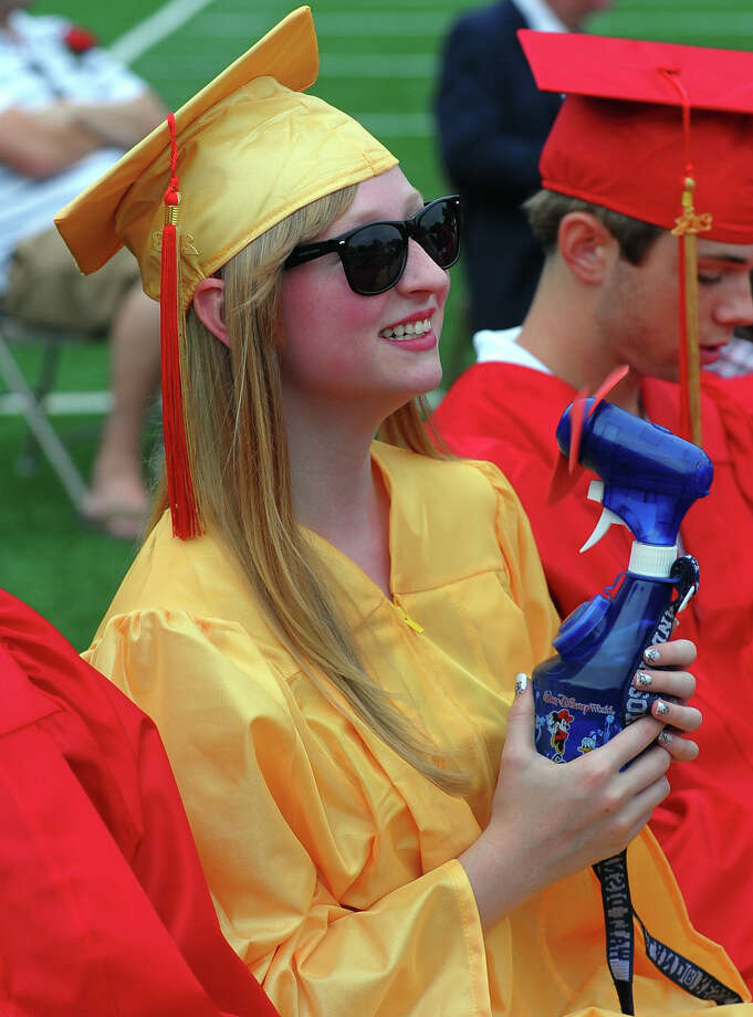 Graduate Karin Wengenroth cools herself off with a fan during Stratford High School's 124th Annual Commencement in Stratford, Conn. on Wednesday June 26, 2013. Photo: Christian Abraham / Connecticut Post