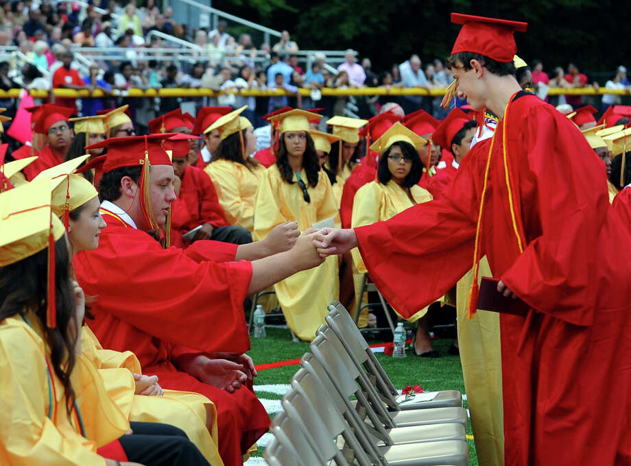 Graduate Zachary Scaefer, right, gives a fist bump to fellow grad and friend Connor Bodington, during Stratford High School's 124th Annual Commencement in Stratford, Conn. on Wednesday June 26, 2013. Photo: Christian Abraham / Connecticut Post