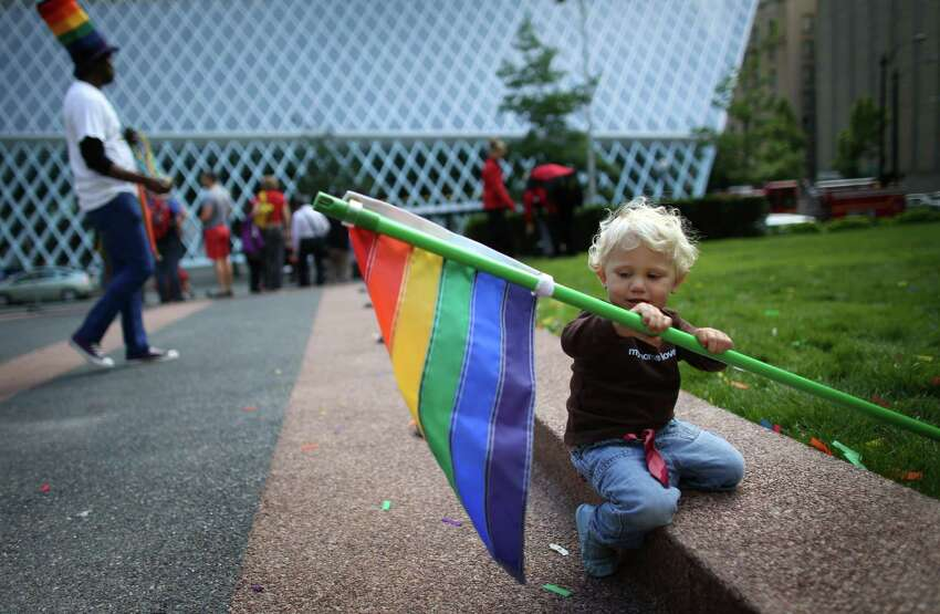 Arly Warn-Johnston, 19 months, holds a flag during a rally on Wednesday, June 26, 2013 in front of the William Kenzo Nakamura United States Court of Appeals in downtown Seattle. His mothers, Jennifer Johnston and Dana Warn, were married in California. Hundreds gathered there Wednesday afternoon after the United States Supreme Court struck down the Defense of Marriage Act and dismissed California's Proposition 8.