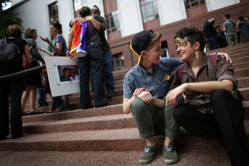 Ander Lyon, left, and Lana McMullen sit on the steps of the William Kenzo Nakamura United States Court of Appeals in downtown Seattle. Hundreds gathered there on Wednesday, June 26, 2013 after the United States Supreme Court struck down the Defense of Marriage Act and dismissed California's Proposition 8.