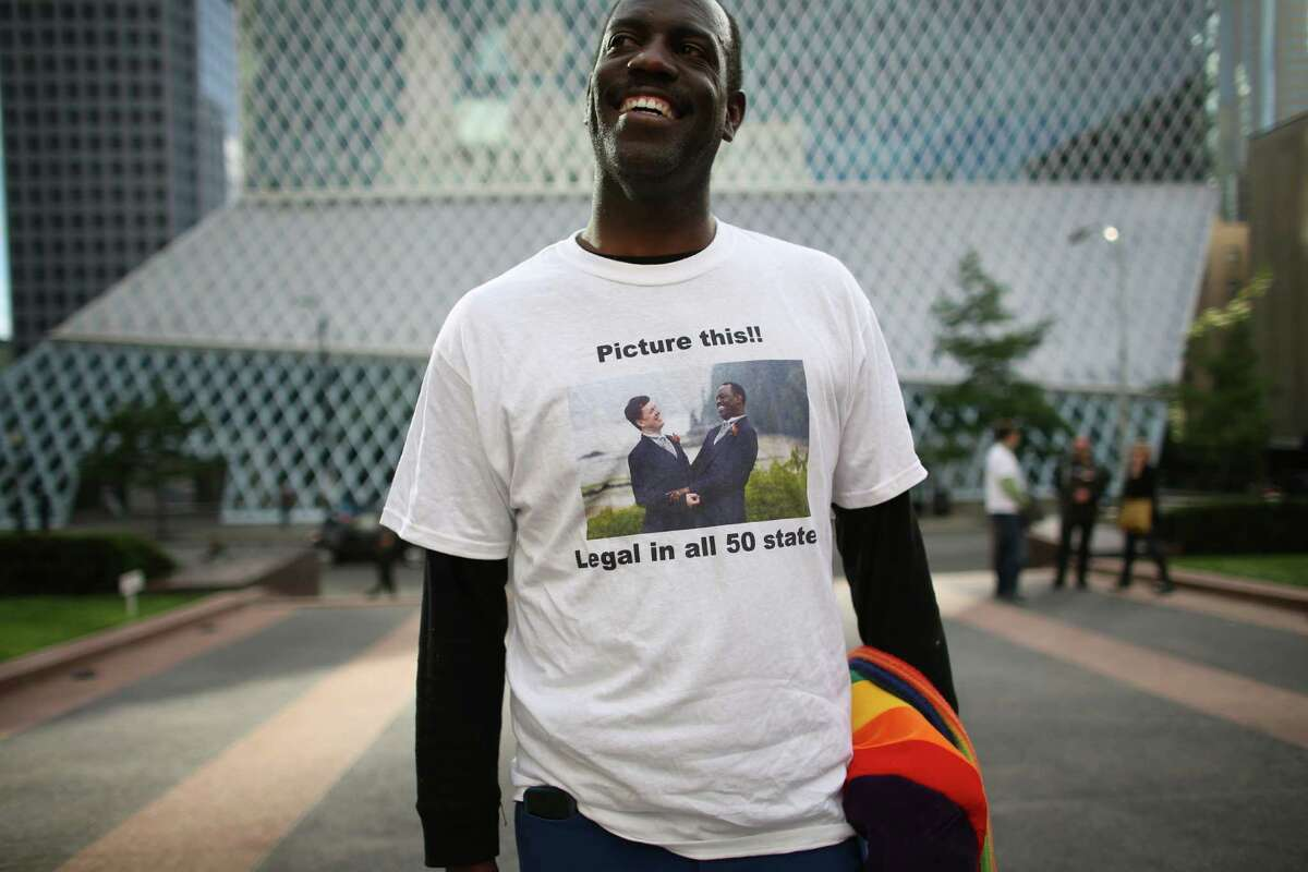Chris Porter wears a shirt showing a photo from the marriage to his husband on Wednesday, June 26, 2013 in front of the William Kenzo Nakamura United States Court of Appeals in downtown Seattle. Hundreds gathered there Wednesday afternoon after the United States Supreme Court struck down the Defense of Marriage Act and dismissed California's Proposition 8.