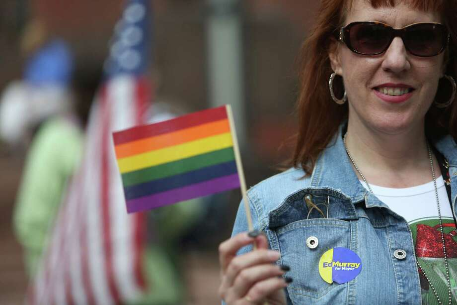 Jane Desilet holds a flag on Wednesday, June 26, 2013 in front of the William Kenzo Nakamura United States Court of Appeals in downtown Seattle. Hundreds gathered there Wednesday afternoon after the United States Supreme Court struck down the Defense of Marriage Act and dismissed California's Proposition 8. Photo: JOSHUA TRUJILLO, SEATTLEPI.COM / SEATTLEPI.COM