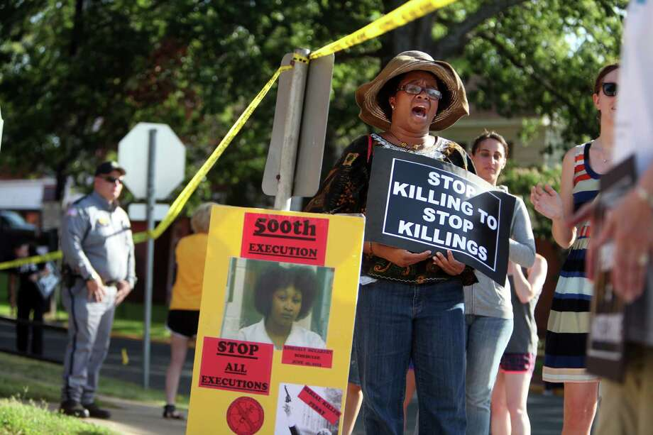 Olinka Green, of Dallas, sings 'Wade in the Water' as she joins protestors outside the Texas State Penitentiary 'Walls Unit' as the execution of Kimberly McCarthy happens on Wednesday, June 26, 2013, in Huntsville. Photo: Mayra Beltran / © 2013 Houston Chronicle