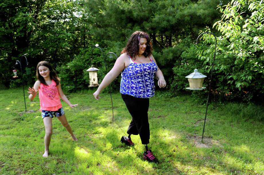 Veteran Marissa Strock,, right, walks with her niece Lexi, 9, on Friday, June 21, 2013, at her mother's home in Sand Lake, N.Y. Strock, who lives in Petersburg, Va., had both her legs blown off in an insurgent attack in iraq in 2005. (Cindy Schultz / Times Union) Photo: Cindy Schultz / 00022927A