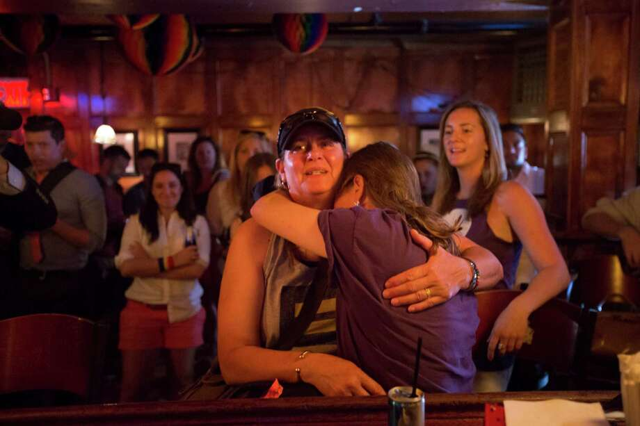 People react to a U.S. Supreme Court ruling at the Stonewall Inn in New York, June 26, 2013. The court ruled Wednesday that the 1996 law denying federal benefits to legally married same-sex couples is unconstitutional, in a sign of how rapidly the national debate over gay rights has shifted. (Ozier Muhammad/The New York Times)  ORG XMIT: XNYT8 Photo: OZIER MUHAMMAD / NYTNS