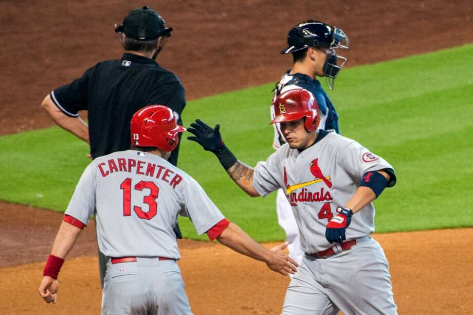 Cardinals first baseman Yadier Molina celebrates with teammate Matt Carpenter after hitting a two-run home run during the first inning.