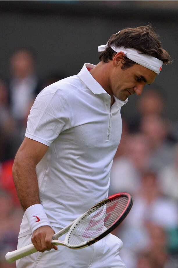 Switzerland's Roger Federer reacts after a point against Ukraine's Sergiy Stakhovsky during their second round men's singles match on day three of the 2013 Wimbledon Championships tennis tournament at the All England Club in Wimbledon, southwest London, on June 26, 2013. AFP PHOTO / CARL COURT -  RESTRICTED TO EDITORIAL USECARL COURT/AFP/Getty Images ORG XMIT: 1170 Photo: CARL COURT / AFP