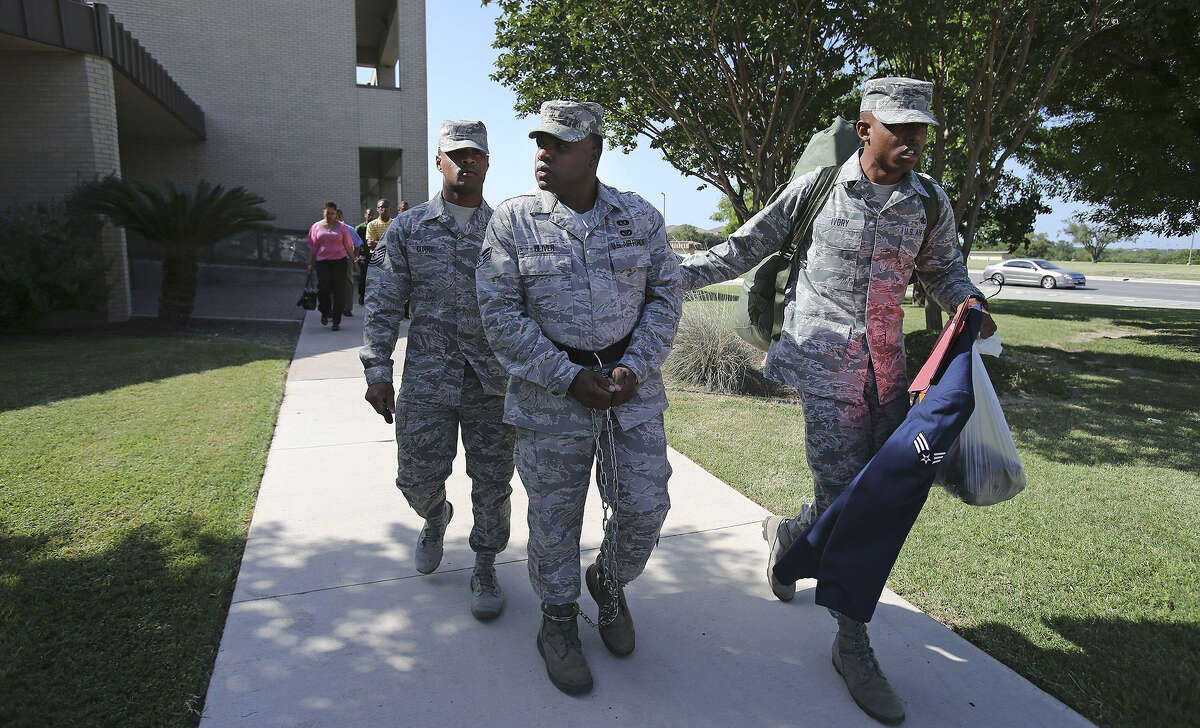 A shackled ex-Senior Airman Christopher Oliver is led away from the 7th Training Wing Headquarters after being sentenced.