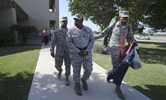 A shackled ex-Senior Airman Christopher Oliver is led away from the 7th Training Wing Headquarters after being sentenced. Photo: Tom Reel / San Antonio Express-News