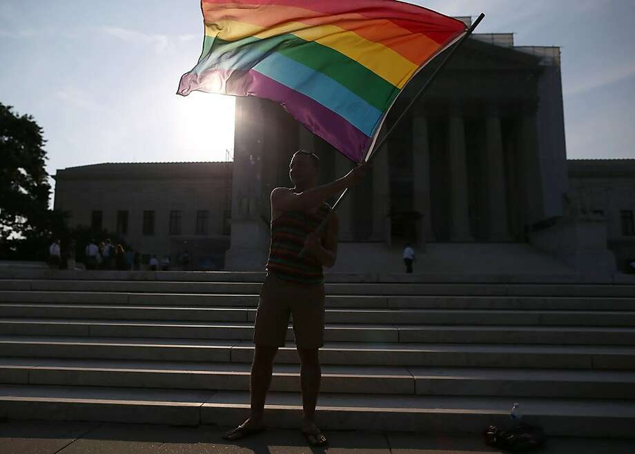 WASHINGTON, DC - JUNE 26:  Gay rights activist Vin Testa of DC, waves a flag  in front of the U.S. Supreme Court building, June 26, 2013 in Washington DC. Today the high court is expected to rule on California's Proposition 8, the controversial ballot initiative that defines marriage as between a man and a woman  (Photo by Mark Wilson/Getty Images) Photo: Mark Wilson, Getty Images