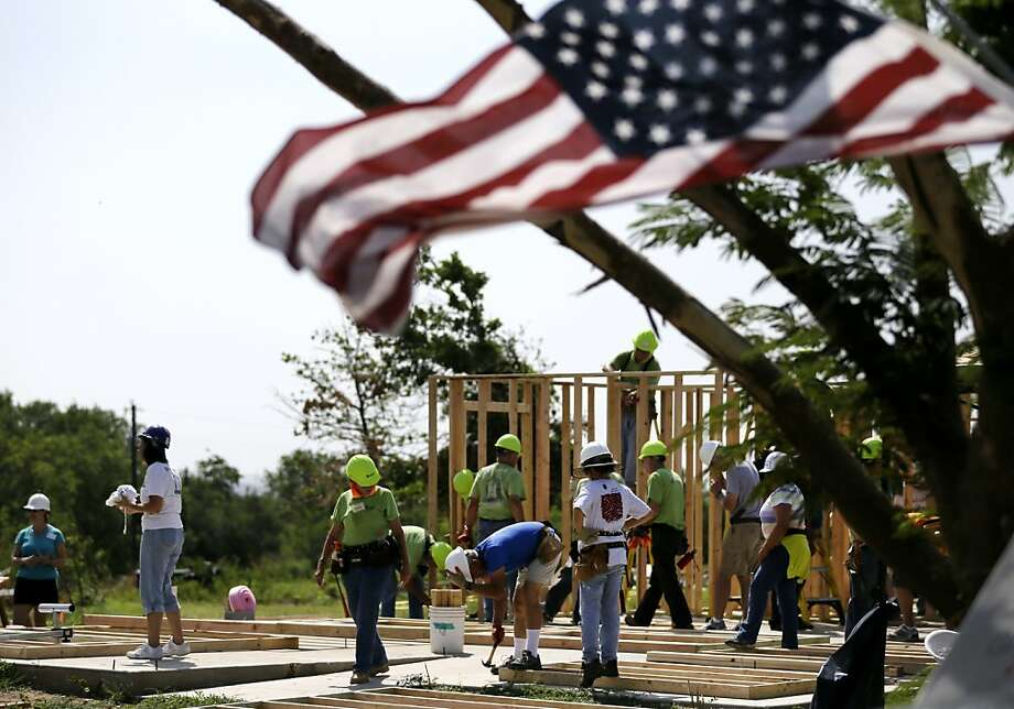An American flag waves in the breeze as volunteers begin work on the home of Olga Hernandez, Wednesday, June 26, 2013, in Granbury, Texas. Volunteers in North Texas are helping a single mother of four rebuild her home after it was destroyed by a tornado last month. (AP Photo/Tony Gutierrez) Photo: Tony Gutierrez, Associated Press