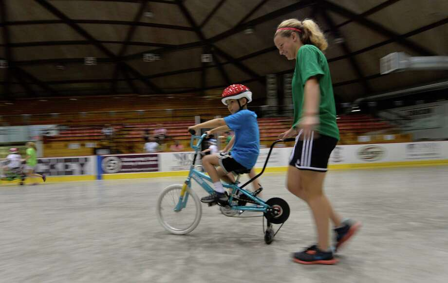 Kayleigh Denney gives a hand to Matt Vichaiwattana during the STRIDE program held at the Achilles Rink June 25, 2013 on the Union College campus in Schenectady, N.Y.  (Skip Dickstein/Times Union) Photo: SKIP DICKSTEIN / 00022947A