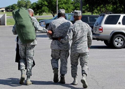 Senior Airman Christopher Oliver is escorted away from the 7th Training Wing Headquarters after receiving sentencing on June 26, 2013. Photo: Tom Reel / San Antonio Express-News