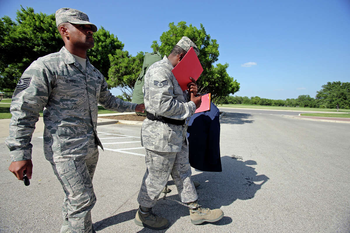 Senior Airman Christopher Oliver is escorted away from the 7th Training Wing Headquarters after receiving sentencing on June 26, 2013.