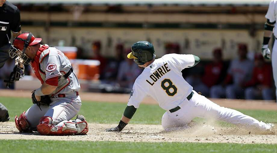 Oakland Athletics' Jed Lowrie (8) scores next to Cincinnati Reds catcher Devin Mesoraco after a double from Brandon Moss during the fourth inning of a baseball game on, Wednesday, June 26, 2013 in Oakland, Calif. (AP Photo/Marcio Jose Sanchez) Photo: Marcio Jose Sanchez, Associated Press