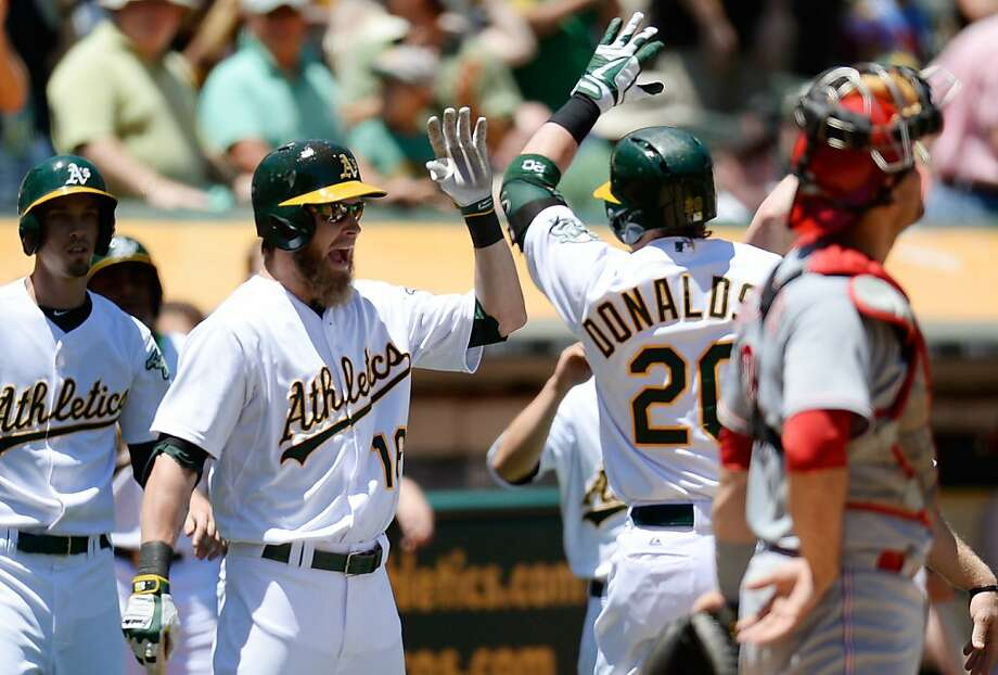 OAKLAND, CA - JUNE 26:  Josh Donaldson #20 of the Oakland Athletics is congratulated by Josh Reddick #16 after Donaldson hit a three-run homer in the fourth inning against the Cincinnati Reds at O.co Coliseum on June 26, 2013 in Oakland, California.  (Photo by Thearon W. Henderson/Getty Images) Photo: Thearon W. Henderson, Getty Images
