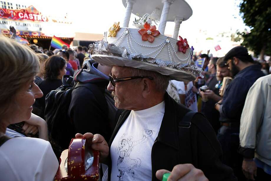 Miguel Gutierrez walks down Castro Street wearing a wedding cake hat to celebrate the Supreme Court decisions on DOMA and Prop. 8. Thousands gathered in the Castro district of San Francisco, Calif., on June 26, 2013, to celebrate the dismissal of the appeal of Proposition 8 by the U.S. Supreme Court. Photo: Carlos Avila Gonzalez, The Chronicle