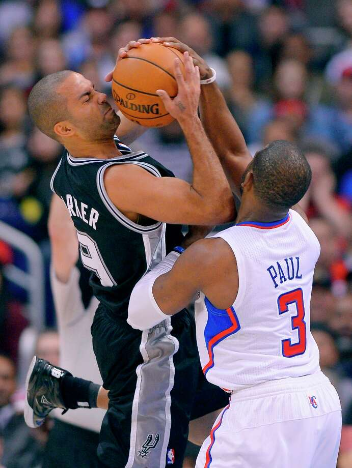 Los Angeles Clippers point guard Chris Paul (right) ties up Spurs point guard Tony Parker during the second half Thursday, Feb. 21, 2013, in Los Angeles. Photo: Mark J. Terrill, Associated Press / AP