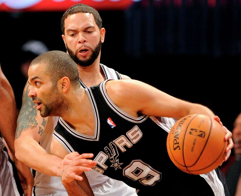 The Spurs' Tony Parker (9) drives the ball against Brooklyn Nets' Deron Williams (8) in the first half, Sunday, Feb. 10, 2013, at Barclays Center in New York. The Spurs won 111-86. Photo: Kathy Kmonicek, Associated Press / FR170189 AP