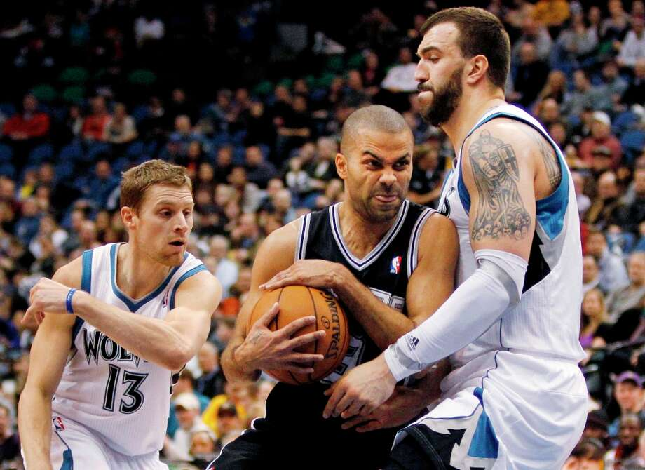 Spurs guard Tony Parker (center) drives around Minnesota Timberwolves center Nikola Pekovic (right) and guard Luke Ridnour (13) during the first half Wednesday, Feb. 6, 2013, in Minneapolis. Photo: Genevieve Ross, Associated Press / FR170496 AP