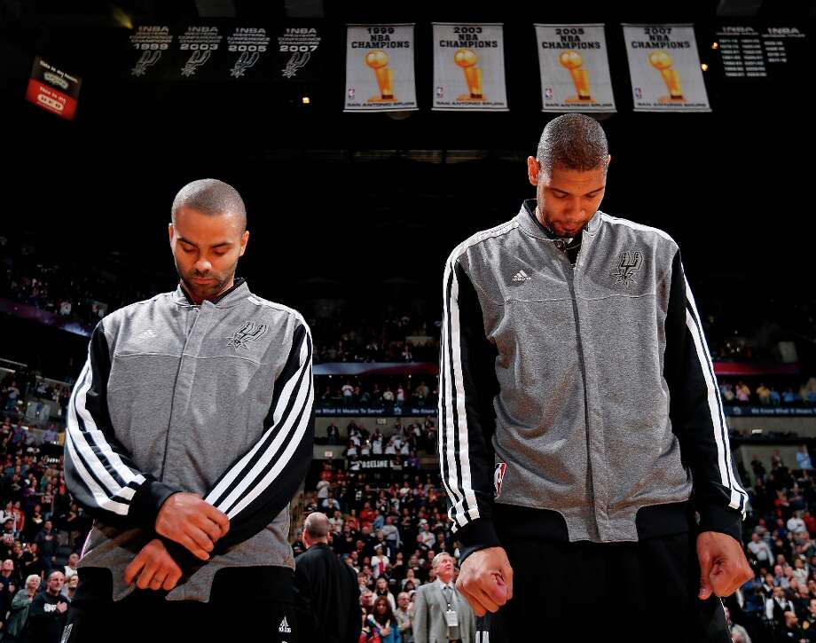 The Spurs' Tony Parker (left) and Tim Duncan stand during the national anthem before the game with the Golden State Warriors on Friday, Jan. 18, 2013 at the AT&T Center. Photo: Edward A. Ornelas, San Antonio Express-News / © 2012 San Antonio Express-News
