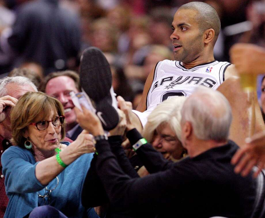 The Spurs' Tony Parker is helped by fans after landing in their seats while chasing a loose ball during second half action against the Indiana Pacers on Monday, Nov. 5, 2012 at the AT&T Center. The Spurs won 101-79. Photo: Edward A. Ornelas, San Antonio Express-News / © 2012 San Antonio Express-News