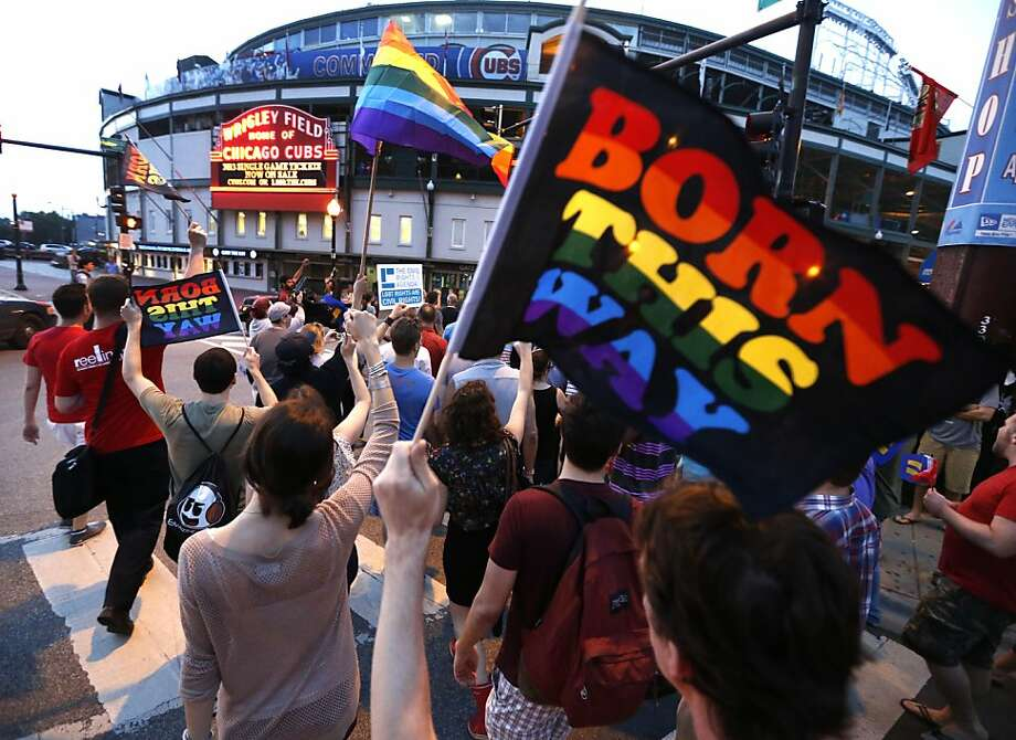 Supporters of gay rights march past Wrigley field following a rally in the Boystown neighborhood of Chicago, Wednesday, June 26, 2013.  In a major victory for gay rights, the Supreme Court on Wednesday struck down a provision of a federal law denying federal benefits to married gay couples and cleared the way for the resumption of same-sex marriage in California. (AP Photo/Charles Rex Arbogast) Photo: Charles Rex Arbogast, Associated Press