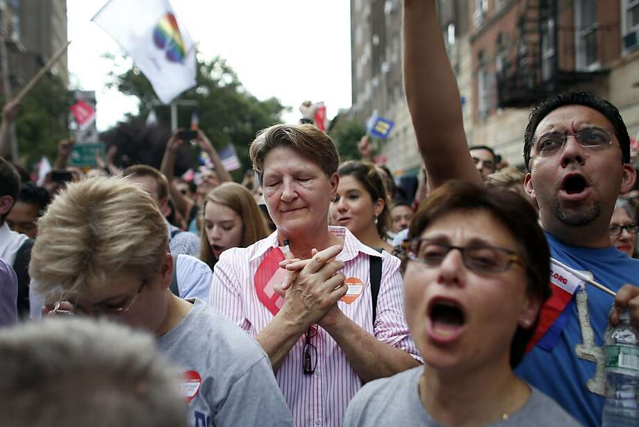 Members of the LGBT community and their supporters gather to celebrate two decisions by the U.S. Supreme Court, one to invalidate parts of the Defense of Marriage Act and another to uphold a lower court ruling that struck down California's controversial Proposition 8, during a rally in New York's Greenwich Village, Wednesday, June 26, 2013. (AP Photo/Jason DeCrow) Photo: Jason DeCrow, Associated Press