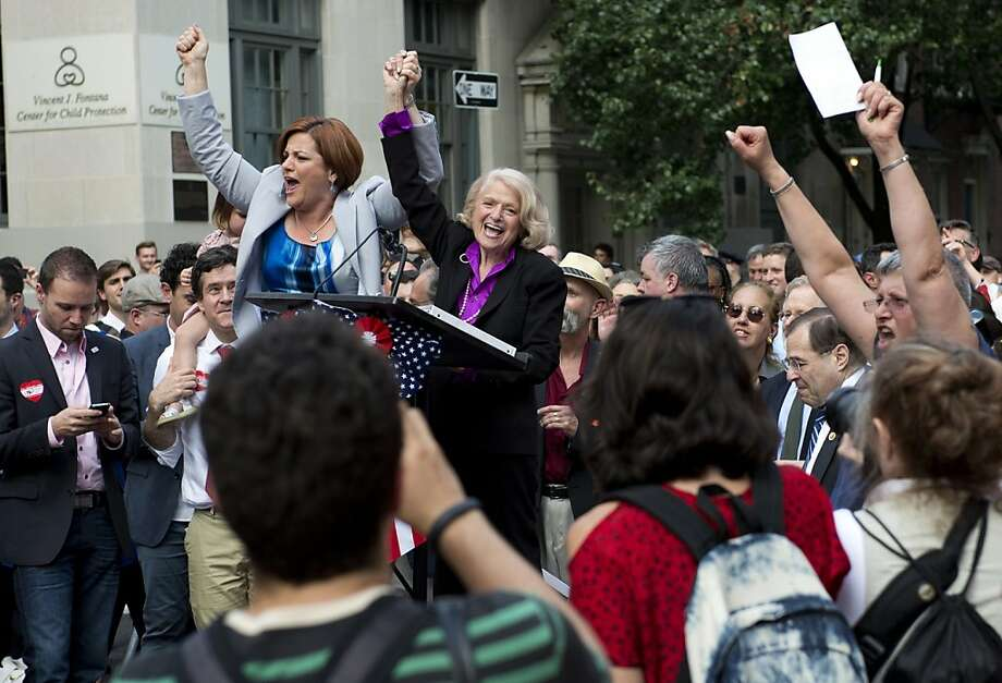 Edie Windsor (R), plaintiff in United States v. Windsor case, and Christine Quinn, speaker of the New York City Council, cheer as they are introduced to the crowd gathered outside Stonewall June 26, 2013 in New York. A large group gathered to celebrate the Supreme Court ruling on the Defense of Marriage Act. AFP PHOTO/Don EmmertDON EMMERT/AFP/Getty Images Photo: Don Emmert, AFP/Getty Images