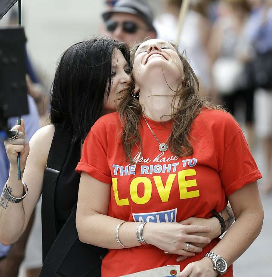 Charlotte Brooks, left, kisses her partner Charlotte D'Ooge, development director for the American Civil Liberties Union, during a celebration rally in Jackson Square in New Orleans, after two Supreme Court decisions supporting gay rights were handed down, Wednesday, June 26, 2013. (AP Photo/Gerald Herbert) Photo: Gerald Herbert, Associated Press